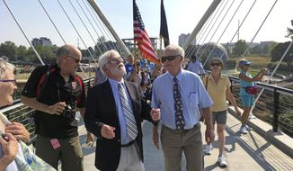 Oregon Senate President Peter Courtney, center right, walks with Salem, Ore., Mayor Chuck Bennett across the Peter Courtney Minto Island Bridge moments after it was dedicated in Salem, Ore., Wednesday, Aug. 2, 2017. The new bridge for walkers and cyclists connects three green spaces in Oregon's capital city. (AP Photo/Andrew Selsky)