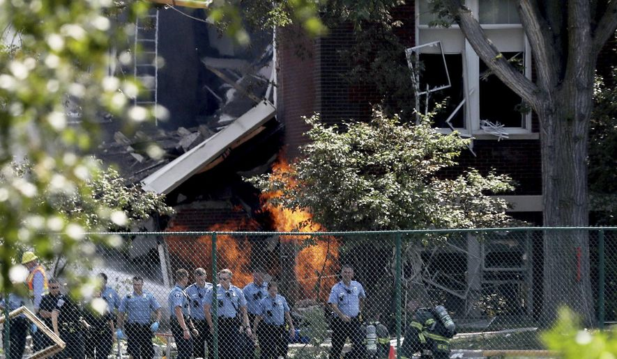 Emergency personnel move away as a gas fire continues to burn following an explosion at Minnehaha Academy Wednesday, Aug. 2, 2017, in Minneapolis. Several people are unaccounted for after an explosion and partial building collapse Wednesday at a Minneapolis school, fire officials said.  (David Joles/Star Tribune via AP)