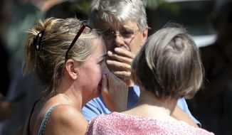 Former Minnehaha Academy employees Elizabeth Van Pilsum, left, and Rick Olson, center, react after an explosion at the school Wednesday, Aug. 2, 2017, in Minneapolis.Several people are unaccounted for after an explosion and partial building collapse Wednesday at the Minneapolis school, fire officials said.  (David Joles/Star Tribune via AP)