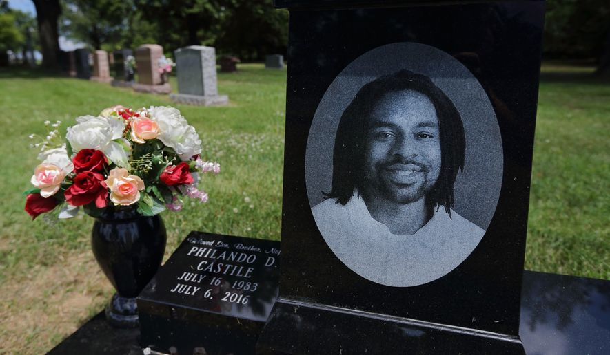 FILE - In this July 6, 2017, file photo, a bouquet of flowers adorns the grave of Philando Castile on the one year anniversary of his death at Calvary Cemetery in St. Louis. Phelix Frazier Sr., the father of Philando Castile, a motorist fatally shot by a suburban Minneapolis police officer last summer, wants a portion of the $3 million settlement reached in his son's death. Frazier is serving a life term in federal prison on drug trafficking charges. (David Carson/St. Louis Post-Dispatch via AP, File)