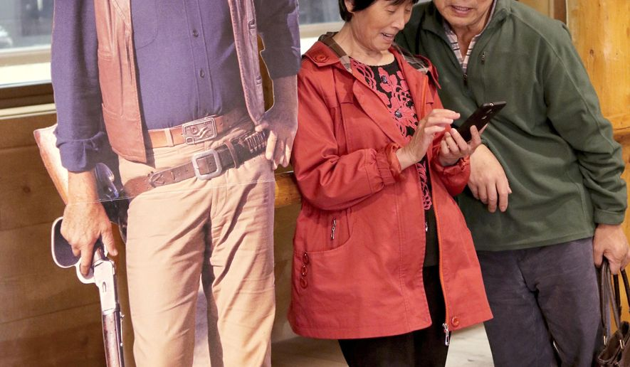 ADVANCE FOR AUG. 2, 2017 AND THEREAFTER - In this June 2017 photo, Quilian Shi, left, and Longcheng Zheng and look at pictures on a phone after posing with a John Wayne cutout at Cody Firearms Experience in Cody, Wyo. Buses carrying perhaps 50 tourists making one-night stopovers or lunch-time pauses make up the majority of Chinese tourists to Cody, but more families are flying to large regional cities such as Salt Lake City or Denver, renting cars and touring on their own. (Raymond Hillegas/The Cody Enterprise via AP)