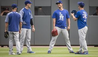 Los Angeles Dodgers' Yu Darvish, second from right, Austin Barnes, left, Alex Wood, and Joc Pederson, right, talk in the outfield as the Dodgers warm up before a baseball game against the Atlanta Braves, Wednesday, Aug. 2, 2017, in Atlanta. Darvish was recently acquired from the Texas Rangers. (AP Photo/John Amis)