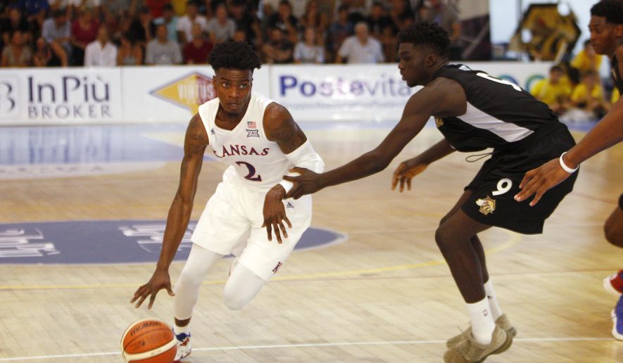 Kansas University's Lagerald Vick, left, is challenged by HSC Roma's Ly-Lee Keller during a basketball game against HSC Roma in Rome, Wednesday, Aug. 2, 2017. (AP Photo/Riccardo De Luca)