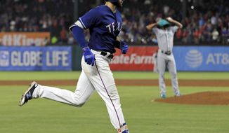 Texas Rangers' Joey Gallo jogs home past Seattle Mariners starting pitcher Ariel Miranda, rear, after hitting a solo home run during the fifth inning of a baseball game, Wednesday, Aug. 2, 2017, in Arlington, Texas. (AP Photo/Tony Gutierrez)