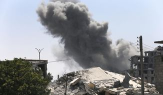 In this July 26, 2017 file photo, black smoke rises from a coalition airstrike which attacked an Islamic State militant position, on the front line on the eastern side of Raqqa, Syria. (AP Photo/Hussein Malla, File)