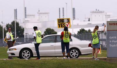 In this Tuesday, Aug. 1, 2017, photo, UAW members set up an informational line outside an employee entrance at the Nissan vehicle assembly plant in Canton, Miss. Most shifts arriving and leaving met union members armed with posters, flyers and singing union chants at each of the plant's employee entrances, reminding workers to vote for the union. The UAW has a vote scheduled Aug. 3-4, on whether it should represent the 3,700 full-time company employees. (AP Photo/Rogelio V. Solis)