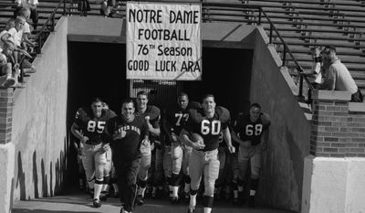 FILE - In this Aug. 31, 1964, file photo, Notre Dame football coach Ara Parseghian and team captain Jim Carroll (60) lead the team out onto the field in Notre Dame Stadium in South Bend, Ind., which was picture day for the team and the day before the season's practices were to begin. Parseghian, who took over a foundering Notre Dame football program and restored it to glory with two national championships in 11 seasons, died Wednesday, Aug. 2, 2017, at his home in Granger, Ind. he was 94. (South Bend Tribune via AP, File)