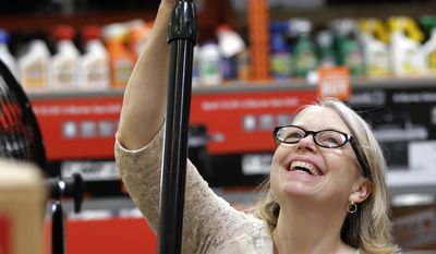 Davi Sobotta smiles as she picks-up a floor fan from a diminishing supply at a Home Depot hardware store ahead of an expected heat wave Tuesday, Aug. 1, 2017, in Seattle. An excessive heat warning for the area began Tuesday afternoon and continues through Friday evening, as unusually hot weather will bring temperatures nearing a peak of 100 degrees on Thursday. (AP Photo/Elaine Thompson)