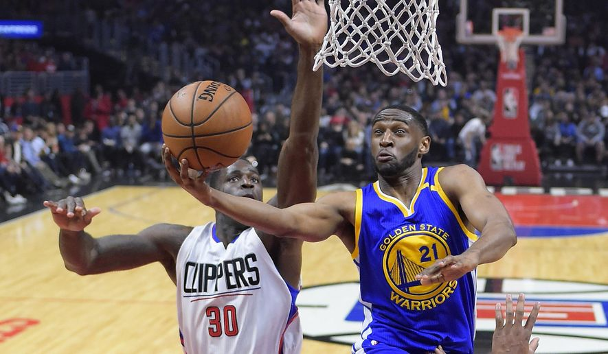 FILE - In this Feb. 2, 2017, file photo, Golden State Warriors guard Ian Clark, right, shoots as Los Angeles Clippers forward Brandon Bass defends during the first half of an NBA basketball game, in Los Angeles. A person familiar with the situation says former Golden State Warriors guard Ian Clark has agreed to play for the New Orleans Pelicans on a one-year, veteran minimum contract. The person spoke to The Associated Press on condition of anonymity Wednesday morning, Aug. 2, 2017, because the signing was not yet official. (AP Photo/Mark J. Terrill, File)