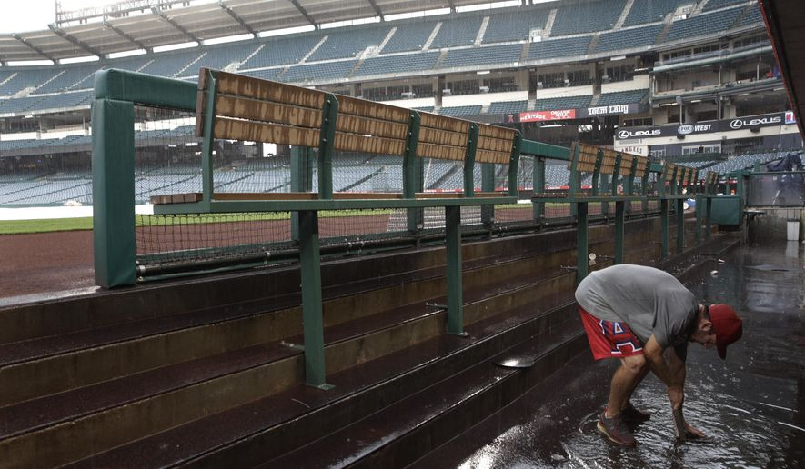 Heavy rain falls as a grounds crew member works on a clogged drain in the flooded dugout before a baseball game between the Los Angeles Angels and the Philadelphia Phillies, Tuesday, Aug. 1, 2017, in Anaheim, Calif. (AP Photo/Jae C. Hong)