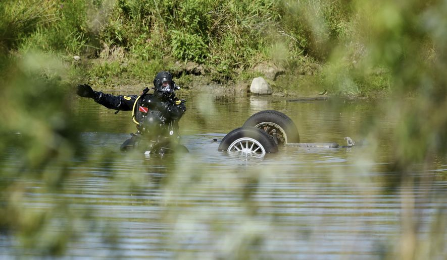 Officials work at a scene where a vehicle was found submerged in a small body of water near the intersection of Pleasant Lake and Parker roads in Freedom Township, Mich., on Monday, July 31, 2017. The body of a man has been recovered from the motor vehicle that was found overturned in a pond in southeastern Michigan. (Melanie Maxwell/The Ann Arbor News via AP)