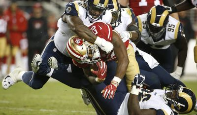 FILE - In this Sept. 12, 2016, file photo, Los Angeles Rams defensive tackle Dominique Easley, top, and defensive tackle Cam Thomas (92) tackle San Francisco 49ers running back Carlos Hyde (28) during the second half of an NFL football game in Santa Clara, Calif. A person with knowledge of the situation says Los Angeles Rams' Dominique Easley is expected to miss the season with a torn knee ligament. The source spoke to The Associated Press on condition of anonymity on Wednesday, Aug. 2, 2017,  because the Rams hadn't announced the severity of the injury for Easley, a likely starter this season.  (AP Photo/Tony Avelar, File)