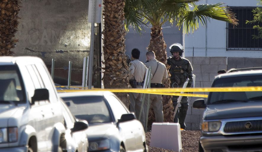Metro Police officers confer near a shooting scene in Las Vegas, Tuesday, Aug. 1, 2017. Police in Las Vegas say an officer is in stable condition at a hospital after being shot while responding to a report of a suspicious vehicle. (Steve Marcus/Las Vegas Sun via AP)