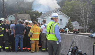 Emergency officials and CSX personnel gather near the site of a freight train derailment, Wednesday, Aug. 2, 2017, in Hyndman, Pa. A freight train carrying hazardous materials partly derailed early Wednesday, setting train cars and a garage on fire and prompting emergency officials to evacuate nearby residents.  (Steve Bittner/The Cumberland Times-News via AP)