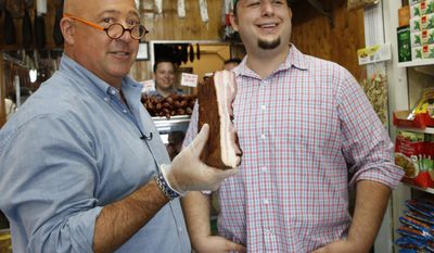 "In this photo taken Thursday, July 20, 2017, ""Bizarre Foods"" host Andrew Zimmern, left, holds a slab of Carska bacon after savoring a small piece of it at Muncan Meats in Astoria, Queens, in New York. Marko Stefanovic, grandson of the store's founder, laughs during the visit. A new show debuting in early 2018, ""The Zimmern List,"" will showcase Zimmern's personal favorites, the eateries where he goes when cameras aren't rolling.  (AP Photo/Kathy Willens)"