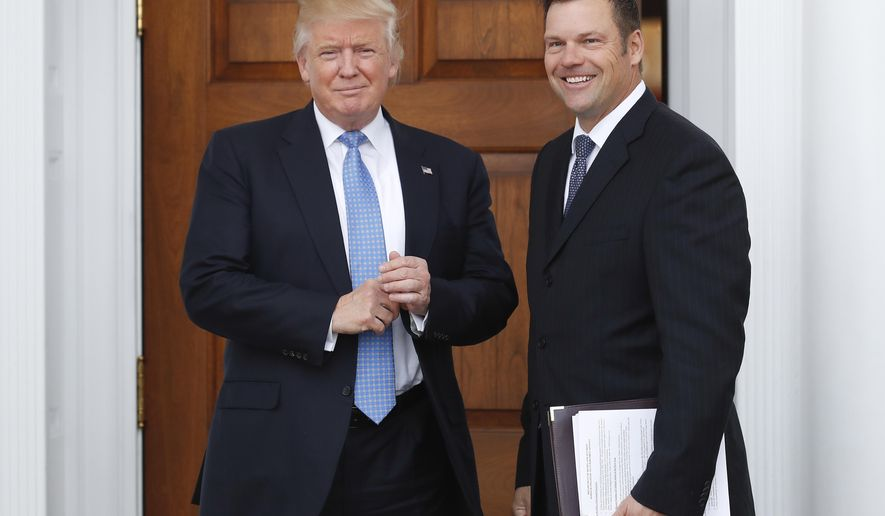 FILE - In this Nov. 20, 2016, file photo, Kansas Secretary of State Kris Kobach, right, holds a stack of papers as he meets with then President-elect Donald Trump at the Trump National Golf Club Bedminster clubhouse in Bedminster, N.J. Kobach who is also vice chairman of Trump's Presidential Advisory Commission on Election Integrity, is seeking to avoid answering questions under oath about two documents containing plans for change U.S. election law. The closed deposition is scheduled for Thursday Aug. 3, 2017. (AP Photo/Carolyn Kaster, File)