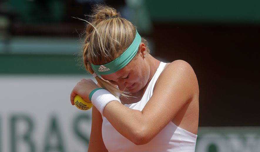 France's Kristina Mladenovic protects her eyes from the clay as she plays Timea Bacsinszky of Switzerland during their quarterfinal match of the French Open tennis tournament at the Roland Garros stadium, Tuesday, June 6, 2017 in Paris. (AP Photo/Michel Euler) **FILE**