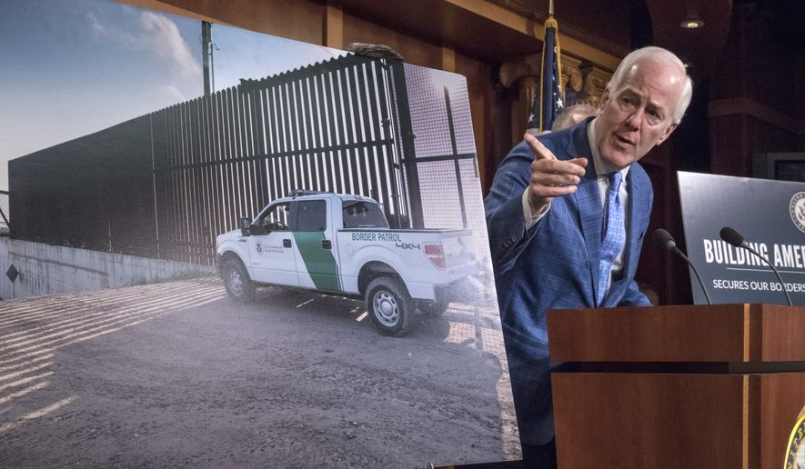 Senate Majority Whip John Cornyn of Texas, points to a poster with an image of barrier on the Texas-Mexico border as he talks to reporters about border security, Thursday, Aug. 3, 2017, on Capitol Hill Washington. (AP Photo/J. Scott Applewhite)