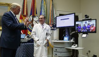 "Veterans Affairs Secretary David Shulkin watches as President Donald Trump talks with a patient during a Veterans Affairs Department ""telehealth"" event, Thursday, Aug. 3, 2017, in the Roosevelt Room of the White House in Washington. (AP Photo/Evan Vucci)"