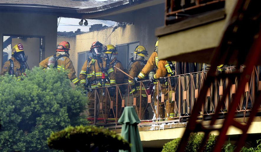 Los Angeles County firefighters inspect the damage after a fire burned through the roof of an apartment building in Arcadia, Calif. on Thursday, Aug. 3, 2017. The fire erupted in the two-story complex early Thursday and spread along the upper floor. Firefighters have largely knocked down the flames, but there's no immediate word on whether there have been any injuries or the fire's cause. (Walt Mancini/Los Angeles Daily News via AP)