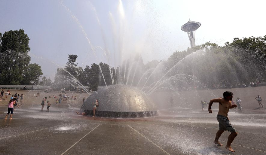 A man races away as a jet begins to spray toward him at the International Fountain at the Seattle Center during a heat wave Wednesday, Aug. 2, 2017, in Seattle. An excessive heat warning for the area continues through Friday evening, as unusually hot weather will bring temperatures nearing a peak of 100 degrees on Thursday. (AP Photo/Elaine Thompson)