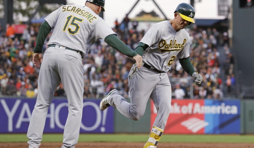 Oakland Athletics' Ryon Healy, right, is greeted by third base coach Steve Scarsone after hitting a two-run home run off San Francisco Giants starting pitcher Matt Moore during the third inning of a baseball game Wednesday, Aug. 2, 2017, in San Francisco. (AP Photo/Eric Risberg)