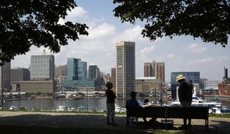 People visit in a park overlooking Baltimore's Inner Harbor, Thursday, Aug. 3, 2017. (AP Photo/Patrick Semansky) ** FILE **