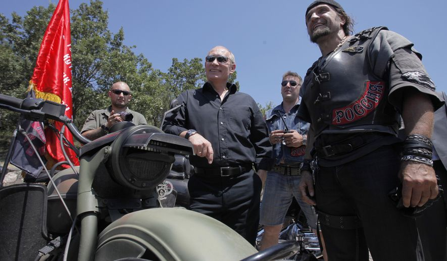 Russian Prime Minister Vladimir Putin, center, and leader of Nochniye Volki (the Night Wolves) biker group, Alexander Zaldostanov, also known as Khirurg (the Surgeon), right, pose for a press attending a meeting of motorbikers at their camp at Gasfort lake  near Sevastopol in Ukraine's Crimea Peninsula, Saturday, July 24, 2010. Putin has lept on a Harley Davidson and roared into a international biker convention in southern Ukraine. Around 5,000 bikers from Europe and beyond are gathered in Sevastopol for the annual festival on Ukraine's Crimea peninsula. (AP Photo/Alexander Zemlianichenko, Pool)