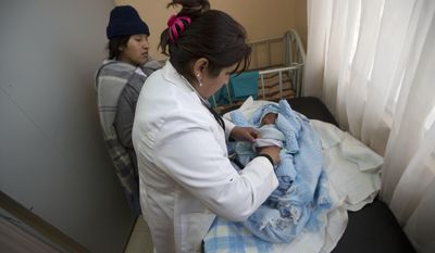 In this June 27, 2017 photo, Dr. Milenkha Chavez gives a routine check-up to 21-day-old Abraham Dilan, who was delivered at home by a midwife, as his mother Mariana Limachi stands by at the Franz Tamayo Health Center in El Alto, Bolivia. A midwife training program officially began in 2013 after Bolivia passed a law recognizing traditional indigenous medicine, including midwifery. (AP Photo/Juan Karita)