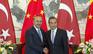 Chinese Foreign Minister Wang Yi at right shakes hands with Turkish Foreign Minister Mevlut Cavusoglu after a joint press conference held at the Diaoyutai State Guesthouse in Beijing, China, Thursday, Aug. 3, 2017. (AP Photo/Ng Han Guan)
