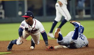 Los Angeles Dodgers' Austin Barnes (15) advances to second base on a wild pitch as the ball gets away from Atlanta Braves second baseman Ozzie Albies during the fifth inning of a baseball game Thursday, Aug. 3, 2017, in Atlanta. (AP Photo/John Bazemore)