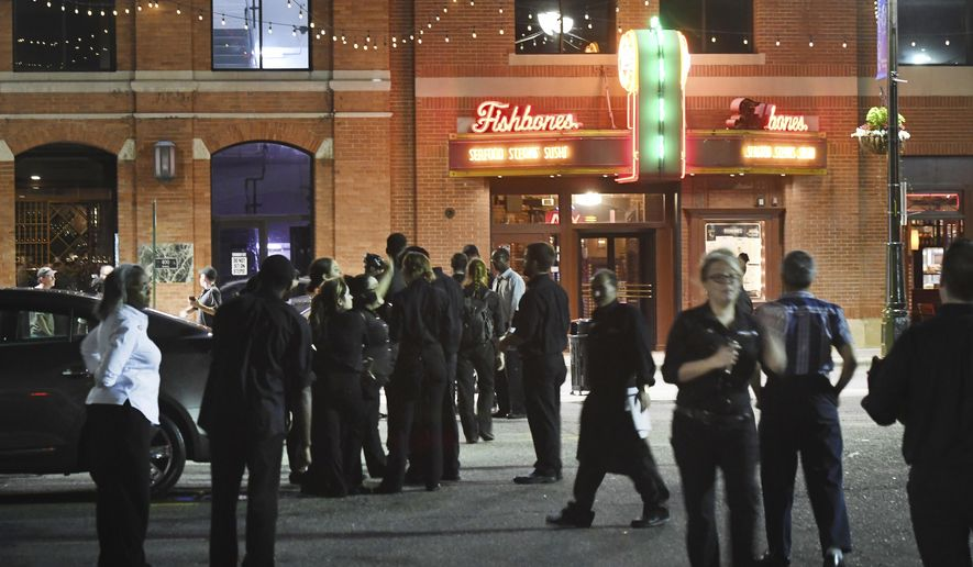 Fishbones employees wait across the street from the restaurant after an explosion in Detroit's Greektown caused evacuations on Wednesday, Aug. 2, 2017. Authorities say an underground electrical cable failure caused explosions in downtown Detroit that sent manhole covers into the air and prompted the evacuation of the restaurant and the Atheneum Suite Hotel. (Daniel Mears/Detroit News via AP)