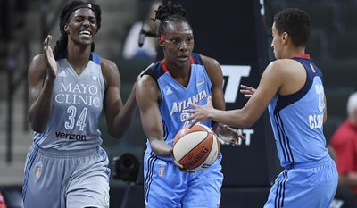 Minnesota Lynx center Sylvia Fowles (34) reacts after losing a rebound to Atlanta Dream forward Sancho Lyttle (20), while Lyttle hands off the ball to guard Layshia Clarendon (23) during the second quarter of a WNBA basketball game Thursday, Aug. 3, 2017, in St. Paul, Minn. (Aaron Lavinsky/Star Tribune via AP)