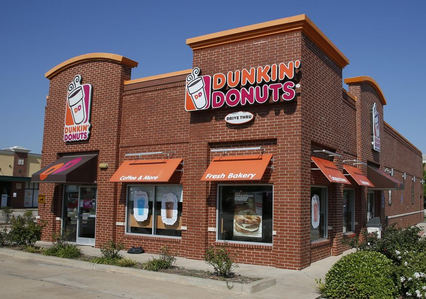 """This Thursday, July 28, 2016, file photo shows a Dunkin' Donuts in Edmond, Okla. Dunkin' is thinking about dumping """"Donuts"""" from its name. A new location in Pasadena, Calif., will be called simply Dunkin', a move that parent company Dunkin' Brands Inc. calls a test. The Canton, Mass.-based company says a few other stores will get the one-name treatment too. (AP Photo/Sue Ogrocki, File)"""