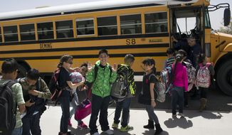 FILE - In this March 31, 2017, file photo, students board a school bus after class at Columbus Elementary School in Columbus, N.M. A high-stakes legal battle focused on the plight of New Mexico's most vulnerable public school students is headed toward an end. After two months of testimony, a state district court judge may reshape the way public schools are funded and guided by the state. Testimony is scheduled to end Friday, Aug. 4, 2017. (AP Photo/Rodrigo Abd, File)