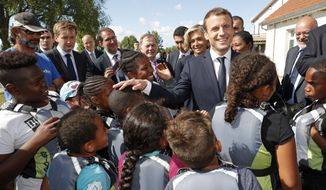 French President Emmanuel Macron greets children as he visits a recreation center in Moisson, east of Paris, France, Thursday, Aug. 3, 2017. French President Emmanuel Macron visits children at a charity holiday program outside Paris to call attention to the problem of families who can't afford to take summer vacation. (Philippe Wojazer/Pool Photo via AP)