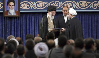 In this photo released by official website of the office of the Iranian supreme leader, Supreme leader Ayatollah Ali Khamenei, left, gives his official seal of approval to President Hassan Rouhani as deputy chief of supreme leader's office Vahid Haghanian looks on in an endorsement ceremony in Tehran, Iran, Thursday, Aug. 3, 2017. A portrait of the late revolutionary founder Ayatollah Khomeini hangs at left. (Office of the Iranian Supreme Leader via AP)