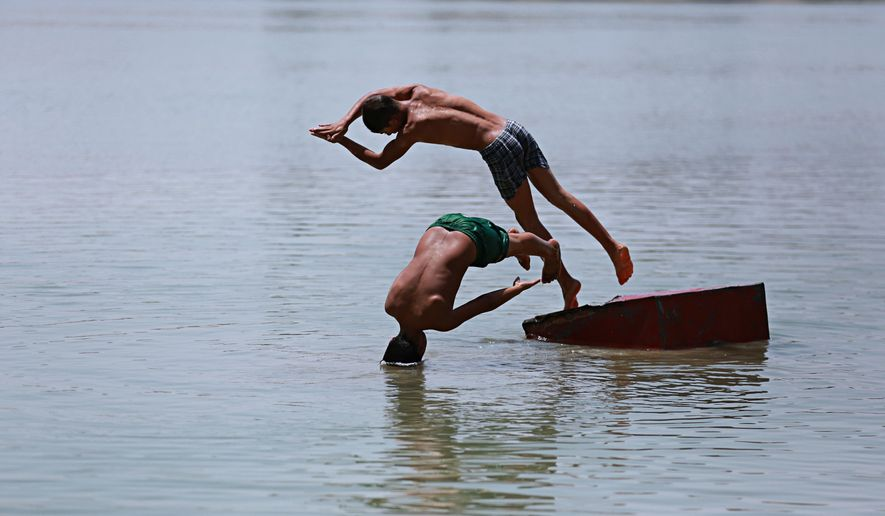 In this photo taken on Friday, July 28, 2017, children swim in the Tigris River to beat the heat in Baghdad, Iraq. Iraq's weather service warned Thursday that temperatures will increase next week in most parts of the country, with the highs expected to reach 51 degrees Celsius, or about 124 degrees Fahrenheit, adding to the daily woes of Iraqi citizens already facing a deteriorated security situation and lack of public services.(AP Photo/Hadi Mizban)