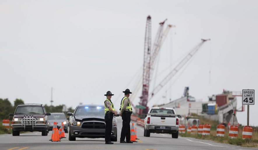A roadblock is set up at the north end of the Bonner Bridge on Thursday, Aug. 3, 2017, on Hatteras Island, N.C. The outage caused by a construction accident forced an estimated 50,000 visitors to leave Hatteras and Ocracoke islands, and others never made it to the popular vacation spots because of evacuation orders that are still in place. (Steve Earley/The Virginian-Pilot via AP)