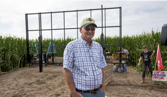 In this July 29, 2017, photo, corn farmer Jim Carlson of Silver Creek, Nebraska, waits to be interviewed by a television reporter while standing in front of solar panels he is building on his land in the proposed path of the Keystone XL pipeline. Despite new uncertainty over whether TransCanada, the builder of the Keystone XL pipeline will continue the project, longtime opponents in Nebraska aren't letting their guard down and neither are law enforcement officials who may have to react to protests if it wins approval. (AP Photo/Nati Harnik)