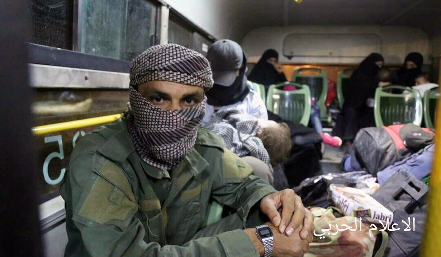 This Thursday, Aug. 3, 2017 photo released by the government-controlled Syrian Central Military Media, shows al-Qaida-linked militants seated in a bus with their families, after being evacuated from the town of Arsal, near the Syrian border, in northeast Lebanon. A large convoy from Lebanon carrying thousands of refugees and al-Qaida-linked militants began arriving at a transfer point in the western Syrian Hama province to complete their journey to the rebel-held Idlib province in northwest Syria. (Syrian Central Military Media via AP)