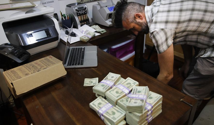 In this June 27, 2017, photo, bundles of $20 bills are placed on a table as Jerred Kiloh, owner of the Higher Path medical marijuana dispensary, prepares a trip to Los Angeles City Hall to pay his monthly tax payment in cash in Los Angeles. For Kiloh, the cash is a daily hassle. It needs to be counted repeatedly to safeguard against loss. State and local taxes must be set aside and stored, sometimes for a month or more. When vendors show up, they get paid in cash, too. (AP Photo/Jae C. Hong)