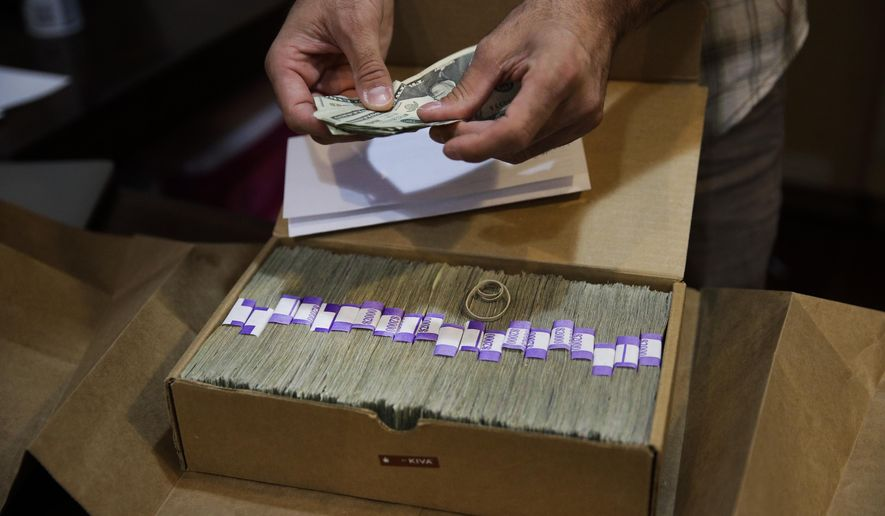 In this June 27, 2017, photo, Jerred Kiloh, owner of the Higher Path medical marijuana dispensary, prepares his monthly tax payment, $40,131.88 in cash in Los Angeles. For Kiloh, the cash is a daily hassle. It needs to be counted repeatedly to safeguard against loss. State and local taxes must be set aside and stored, sometimes for a month or more. When vendors show up, they get paid in cash, too. (AP Photo/Jae C. Hong)