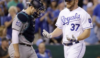 Kansas City Royals' Brandon Moss (37) crosses the plate past Seattle Mariners catcher Mike Zunino after hitting a two-run home run during the fifth inning of a baseball game Thursday, Aug. 3, 2017, in Kansas City, Mo. (AP Photo/Charlie Riedel)