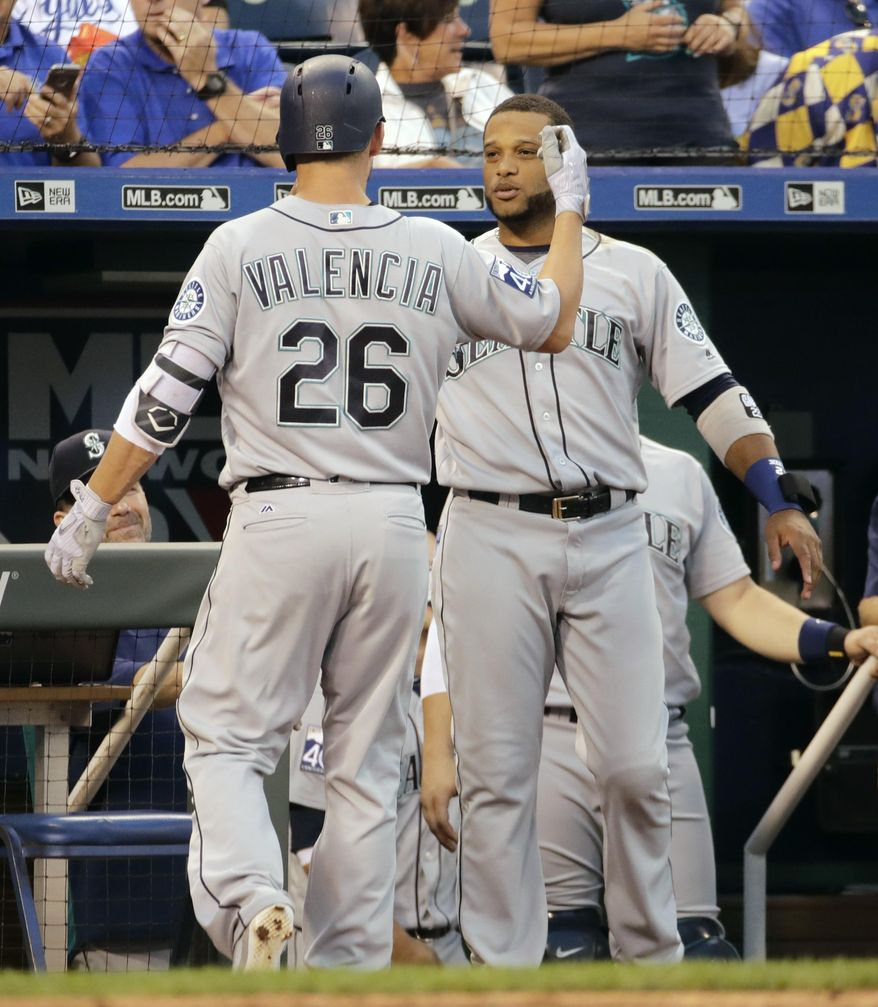 Seattle Mariners' Danny Valencia (26) celebrates with Robinson Cano after hitting a solo home run during the fourth inning of a baseball game against the Kansas City Royals Thursday, Aug. 3, 2017, in Kansas City, Mo. (AP Photo/Charlie Riedel)
