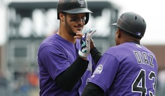 Colorado Rockies' Nolan Arenado, left, is congratulated by first base coach Tony Diaz as Arenado touches first base after drawing a walk with the bases loaded to force in the winning run off New York Mets relief pitcher Hansel Robles in the ninth inning of a baseball game Thursday, Aug. 3, 2017, in Denver. The Rockies won 5-4. (AP Photo/David Zalubowski)