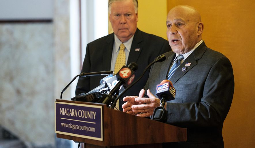 Niagara County Legislator David E. Godfrey, left, looks on as state Assemblyman Angelo J. Morinello calls for the resignation of members of the Niagara Falls water board during a news conference at the Niagara County Courthouse, Thursday, Aug. 3, 2017, in Lockport, N.Y. The call for resignations comes after a discharged of a plume of stinky, black water into the Niagara River near the base of Niagara Falls from the wastewater treatment plant on Saturday, July. 29. (Joed Viera/The Union-Sun & Journal via AP)