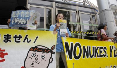 In this Tuesday, Aug. 1, 2017, photo, members of an anti-nuclear pacifist citizens' group protest outside Yokosuka-chuo Station in Yokosuka, south of Tokyo. Residents of Yokosuka city, home to a major U.S. Naval Base near Tokyo, share their thoughts on North Korea and its recent intercontinental ballistic missile launches. (AP Photo/Sherry Zheng)