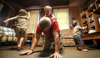 ADVANCE FOR USE SATURDAY, AUG. 5 - In this March 5, 2017 photo, Mike Belisle gives his grandson Aiden, 2, a ride on his back while Joey, 4, left, and Nicholas, 1, (right) play at their Quincy, Fla. The grandparents now have custody of Joey, Aiden and Nicholas Kelsey after the children's parents died from lethal doses of fentanyl, a drug often used for pain relief in terminally ill patients that is at least 50 to 100 times stronger than morphine. (Jacob Langston/Orlando Sentinel via AP)