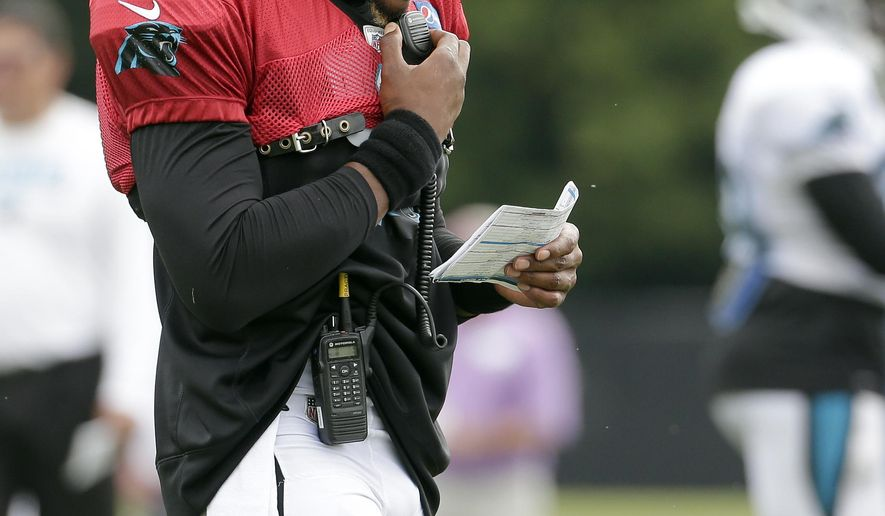 Carolina Panthers' Cam Newton (1) talks on a radio and he looks at plays during practice at the NFL team's football training camp at Wofford College in Spartanburg, S.C., Wednesday, Aug. 2, 2017. (AP Photo/Chuck Burton)
